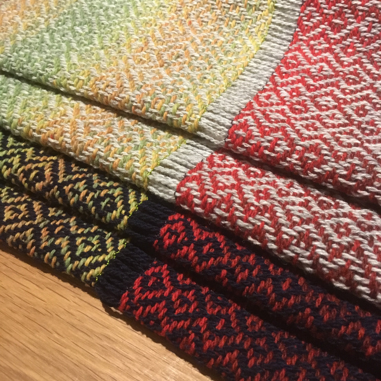 Photo of the finished scarves, still attached to each other by the weft in the gap.