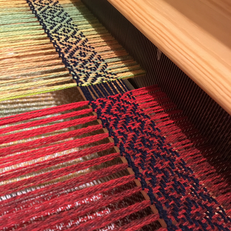 Photo of the front of the loom, showing the scarves being woven next to each other, with the bright green twisted threads slightly visible on one of them.