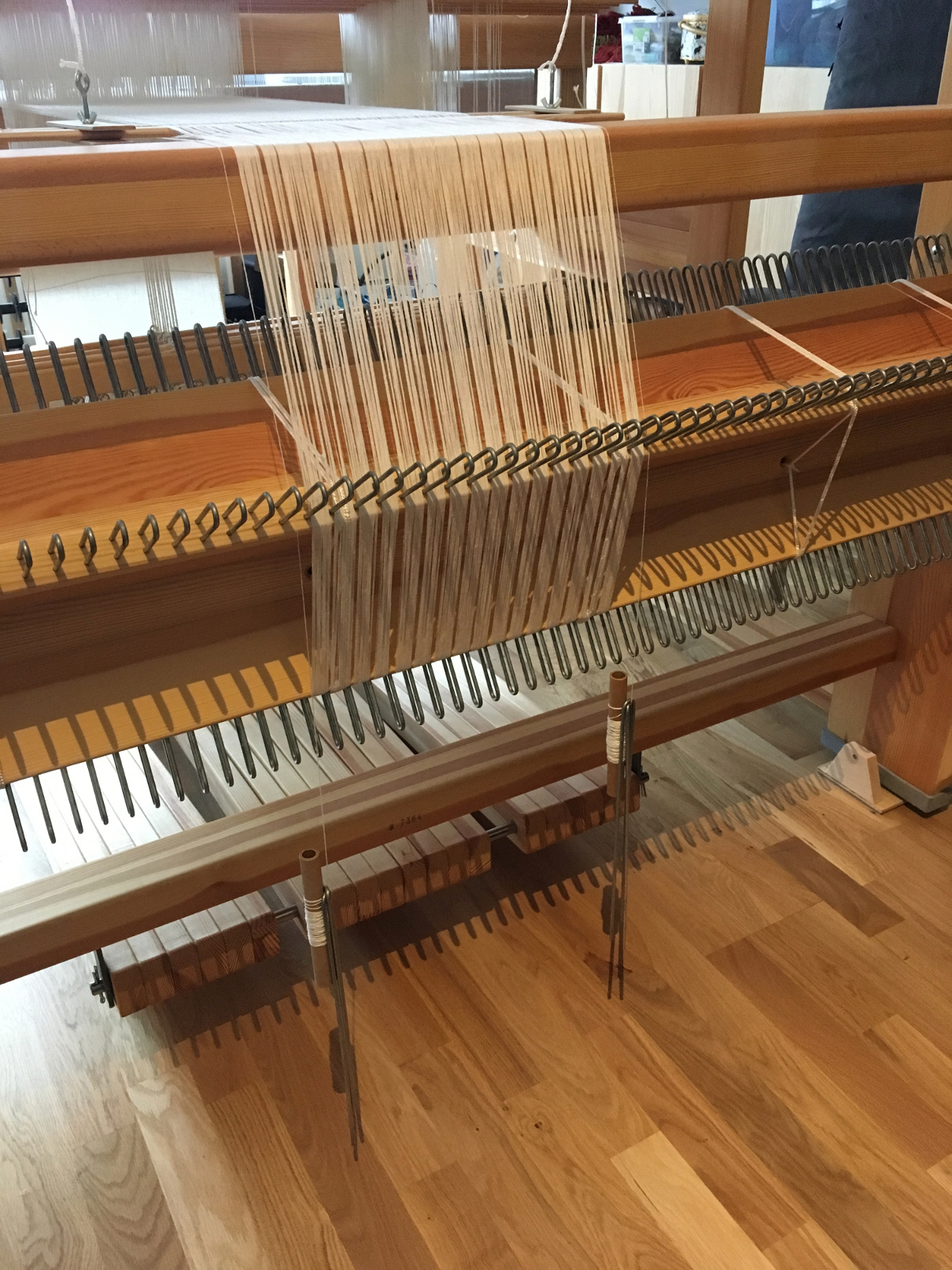 Photograph of the back of a wooden loom, showing the white warp wound on the beam and two extra bobbins dangling on the sides, weighted down.