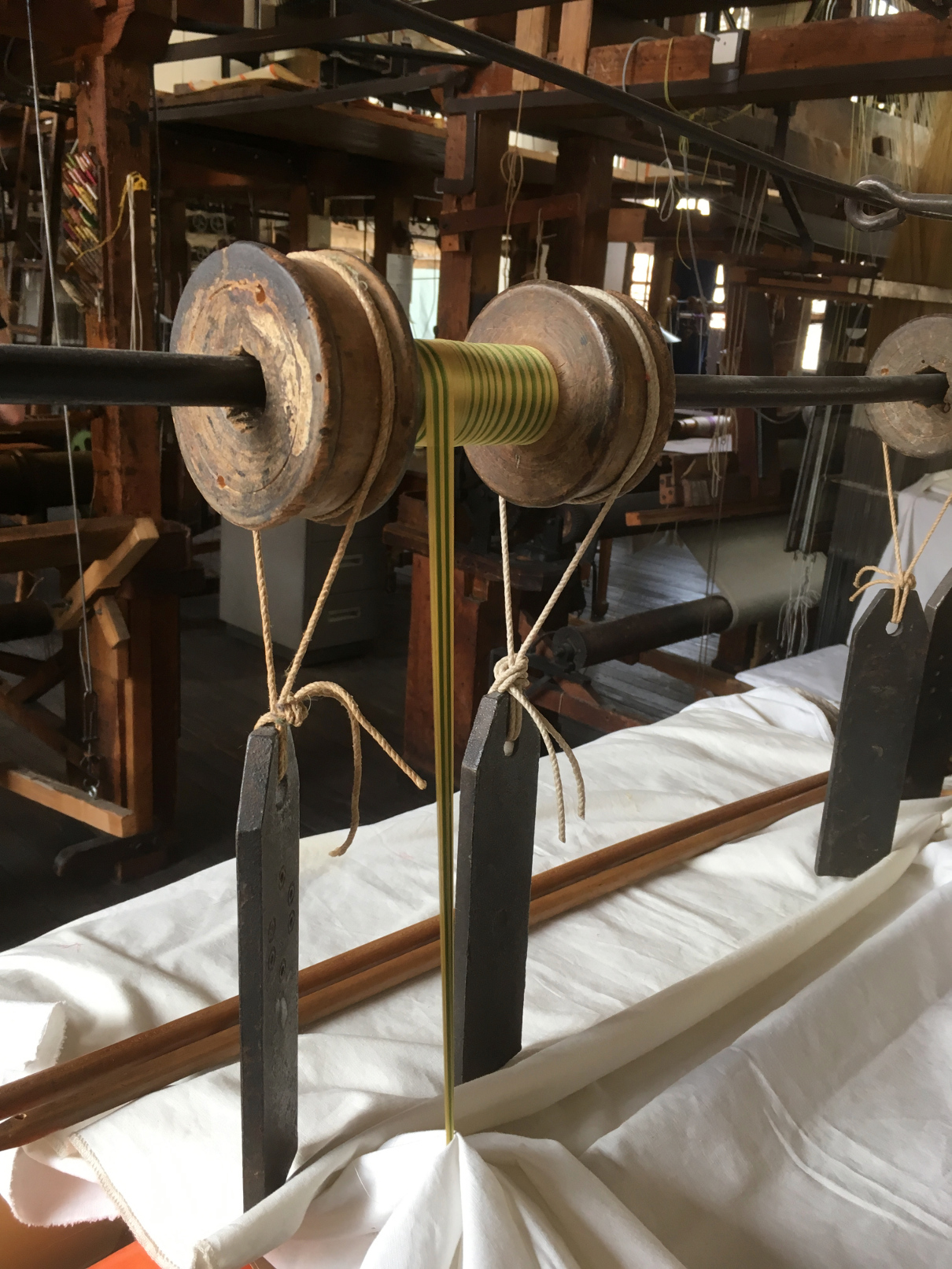 Photograph of a bobbin hanged up in an antique loom, weighted on both sides, with a ribbon's worth of silk wound on it.