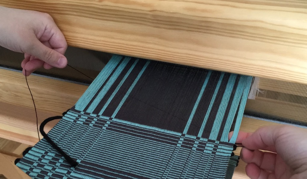 Photograph of the process of opening the sticky shed at the selvedges with fingers. Links to a video of the weaving process described above.
