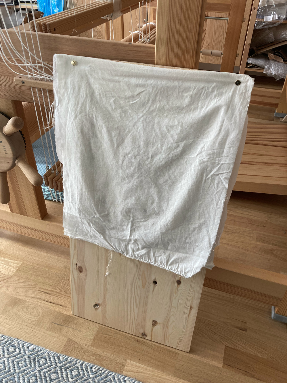 The plank, vertical again, with the wet fabric folded over the embroidery.