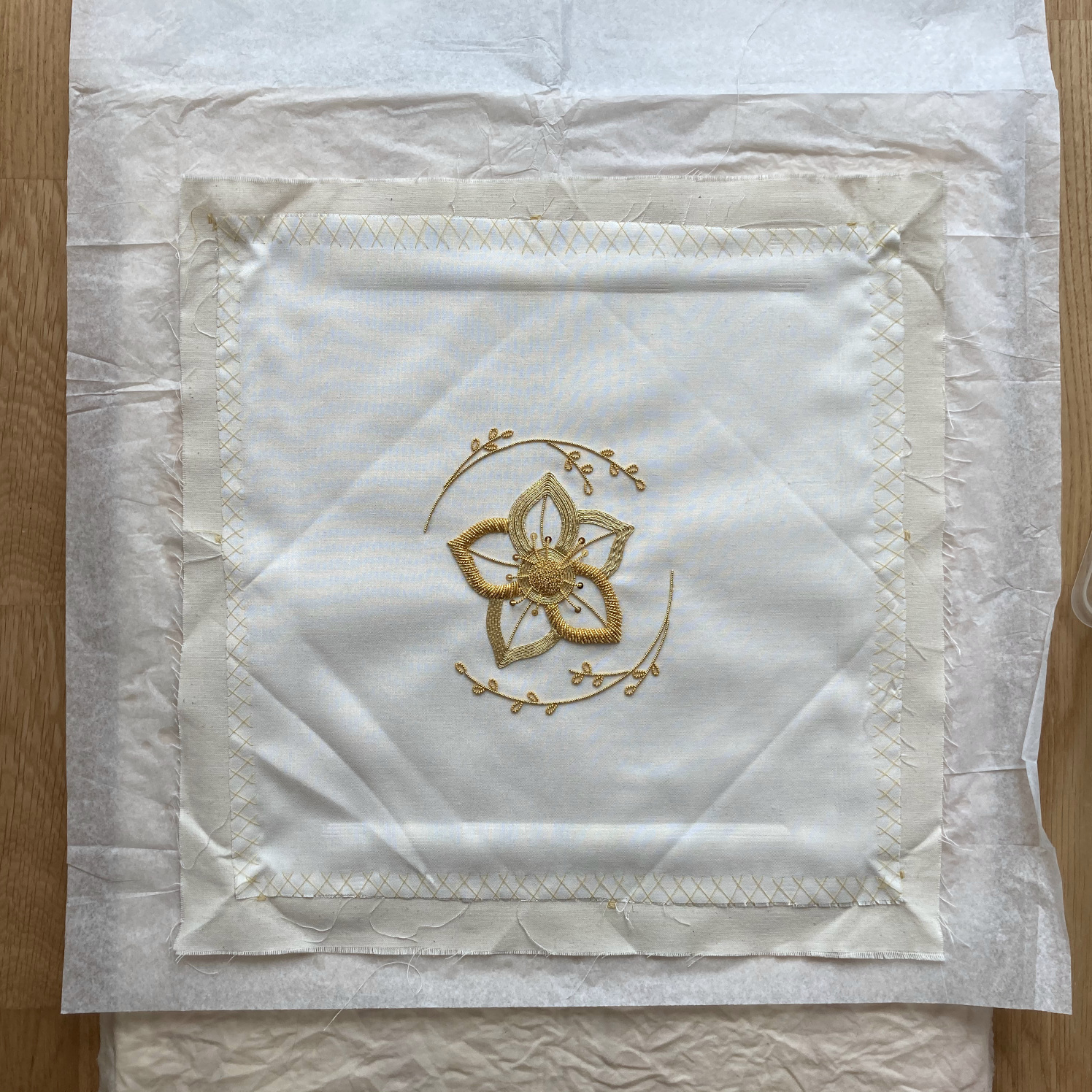 Embroidery laid out on the plank, fabric and silk paper sandwich.