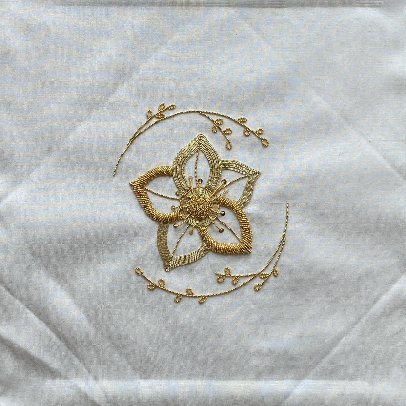 Embroidered flower in golden threads, on fabric with obvious folds and wrinkles.