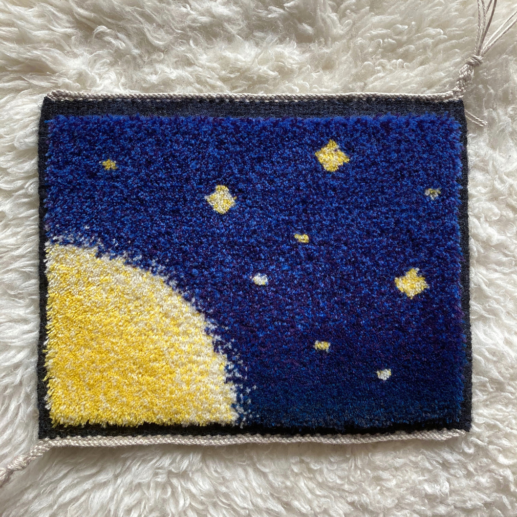 The finished piece: a small horizontal rectangular cut pile carpet, portraying a bright yellow sun in a starry dark sky.