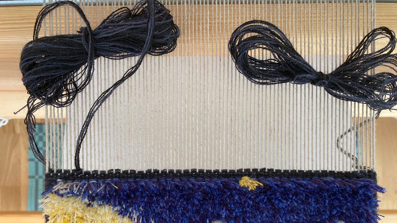 A carpet warp seen from the top, showing the state after the ground rows. A couple dark wefts are visible over the last knotted row.