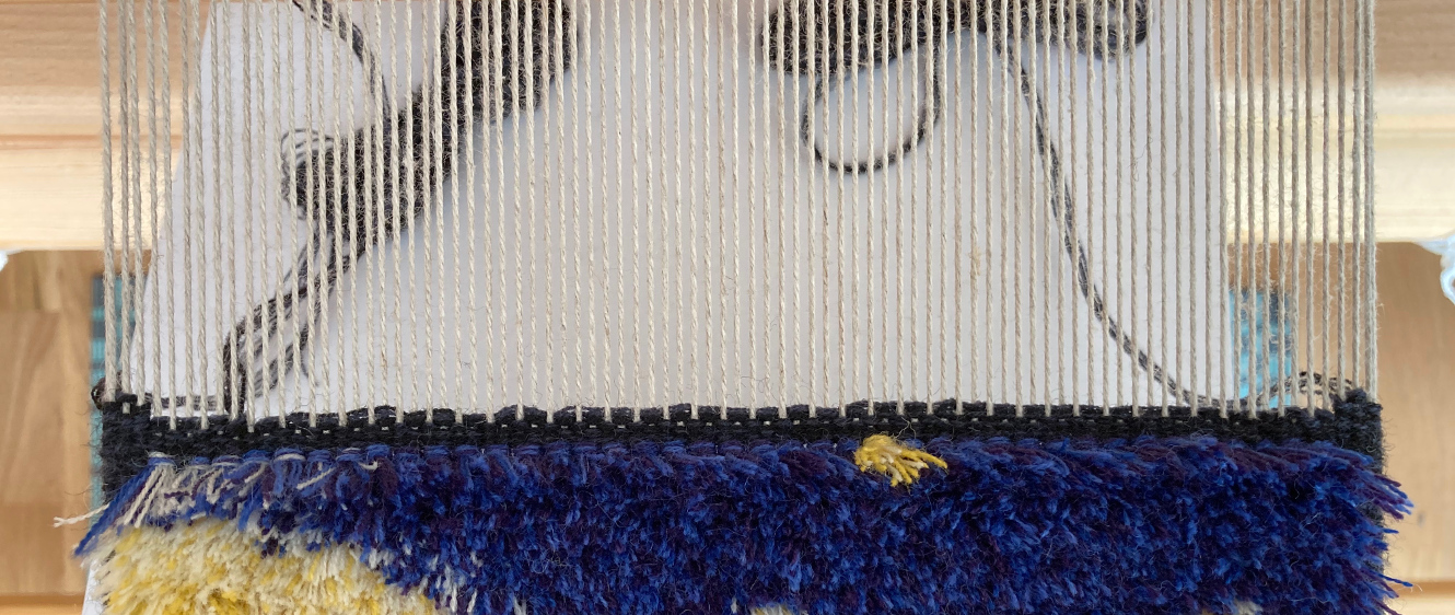 A carpet warp seen from the top, showing the state after the knot row selvedges are made. A couple dark wefts are visible over the last knotted row, with extra build-up on the selvedges.
