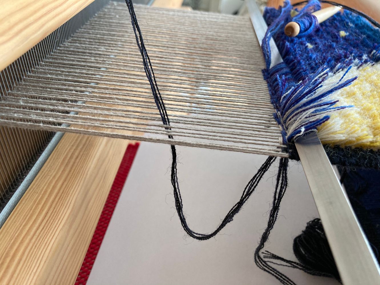 A carpet warp seen from the side, showing a ground weft loop pulled down between warp ends.