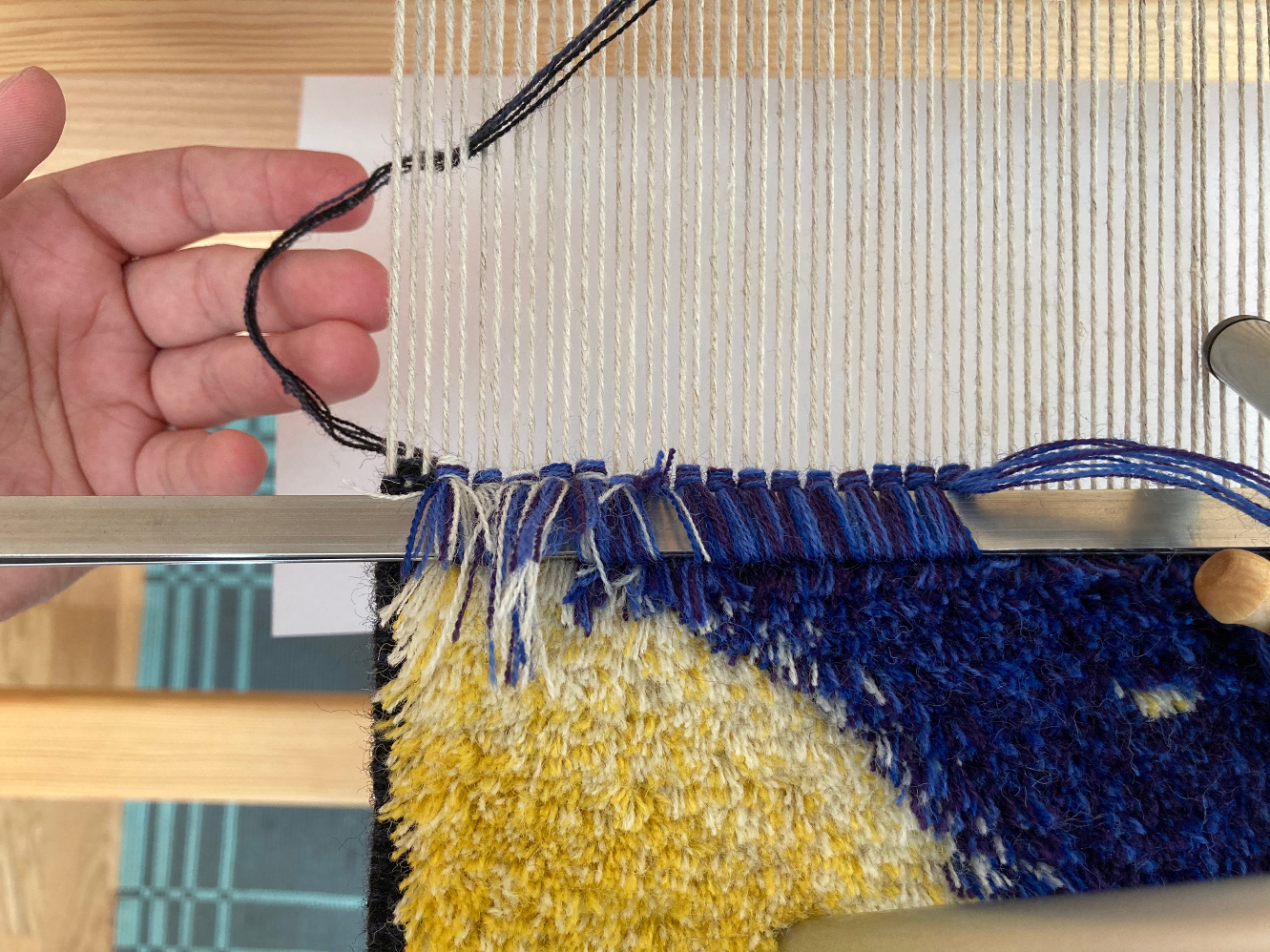 A carpet warp seen from the top, showing a ground weft loop pulled down between warp ends.