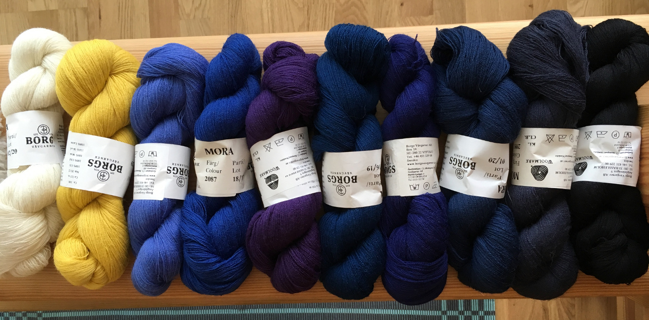 Ten skeins of thin wool yarn, mostly in deep dark blue-purple shades, plus yellow and white.