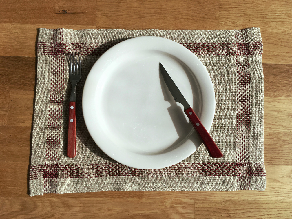 A placemat with a red lace weave border, with a plate, fork and knife on it.